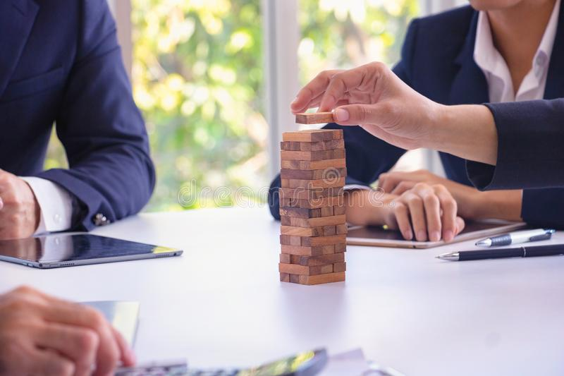 Body part Business engineers plays Jenga game and Orange hat. royalty free stock photo