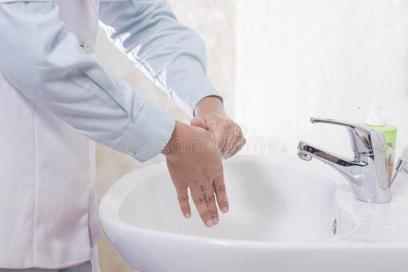 Body part of female doctor washing her hand rubbing thumb in the sink with soap foam royalty free stock photography