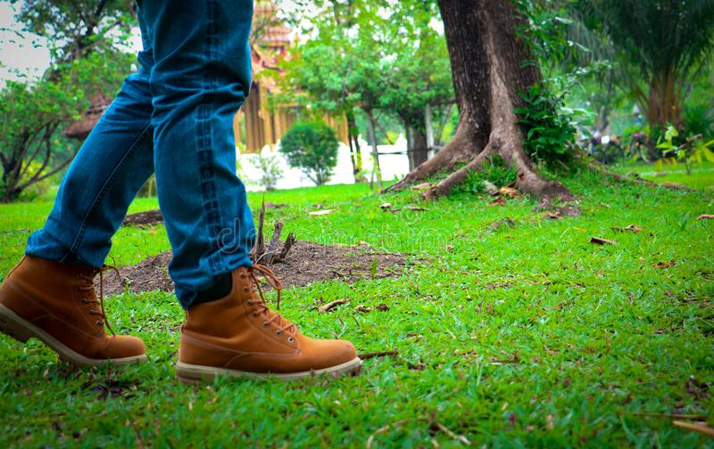 Body part a man walking. He walking on grass background. He wear black shoes stock photos