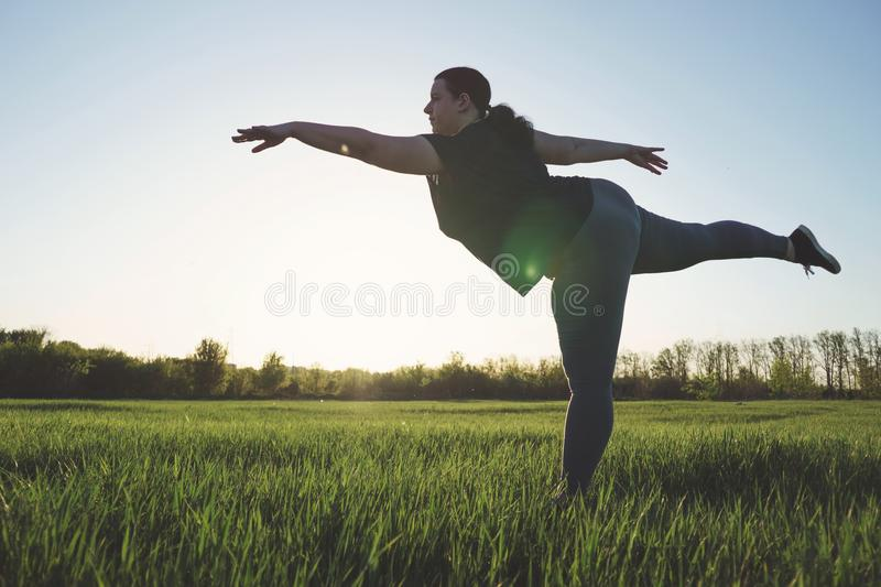 Overweight woman dancing outdoors. Freedom concept stock photos