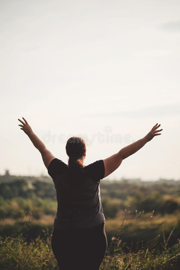 Overweight woman celebrating rising hands to sky stock image
