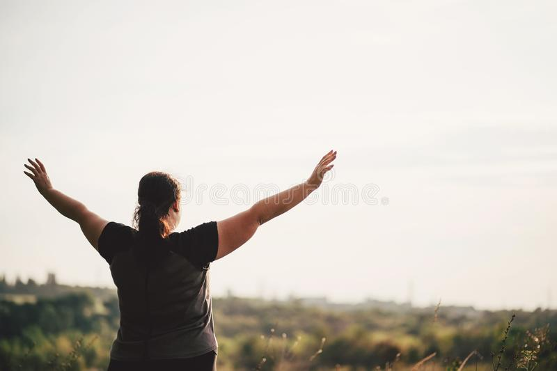 Overweight woman rising hands to the sky stock photography