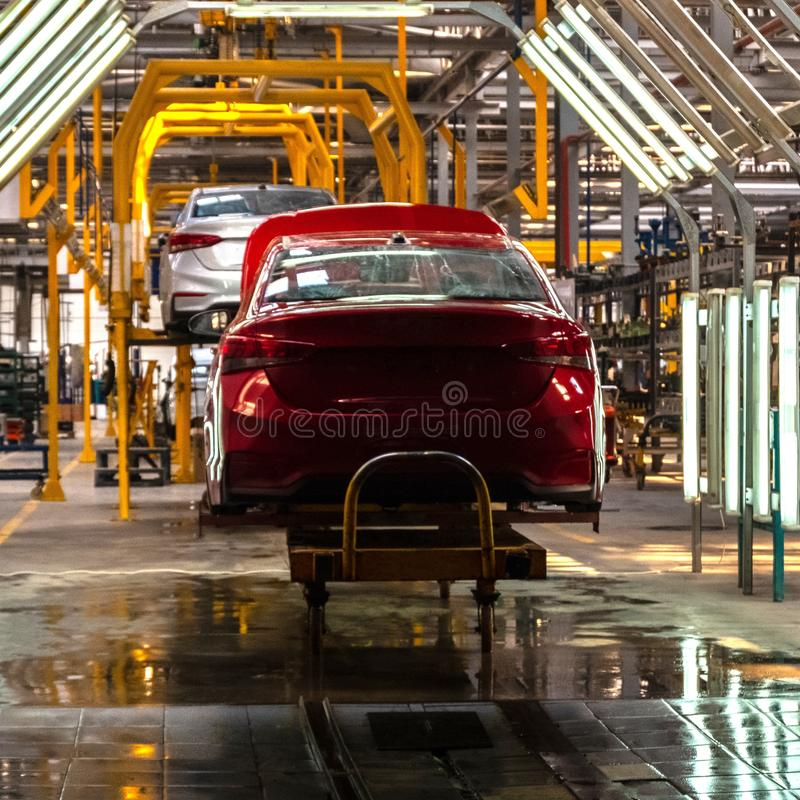 The body of the red car on the production line. Plant vehicles or car repair shop. Auto tuning studio. Square frame stock photos