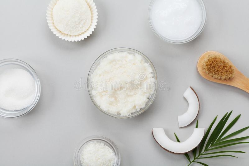 Body scrub of coconut oil, sugar and shavings in glass jar top view. Homemade cosmetic for peeling and spa care. Flat lay. Body scrub of coconut oil, sugar and stock images