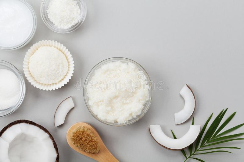Body scrub of coconut oil, sugar and shavings in glass jar top view. Homemade organic cosmetic for peeling and spa care. Flat lay. Body scrub of coconut oil stock photography