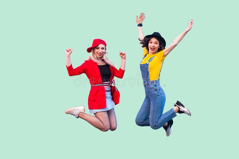 Body size portrait of two happy screaming stylish hipster girls in fashionable clothes are jumping up in the air and looking at. Camera with raised arms. Indoor royalty free stock image