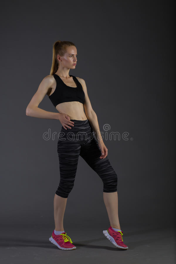 Body of slim female in activewear doing posin on gray low key, perfect blonde. Body of slim female in activewear doing posin on gray low key, perfect sport woman royalty free stock photo