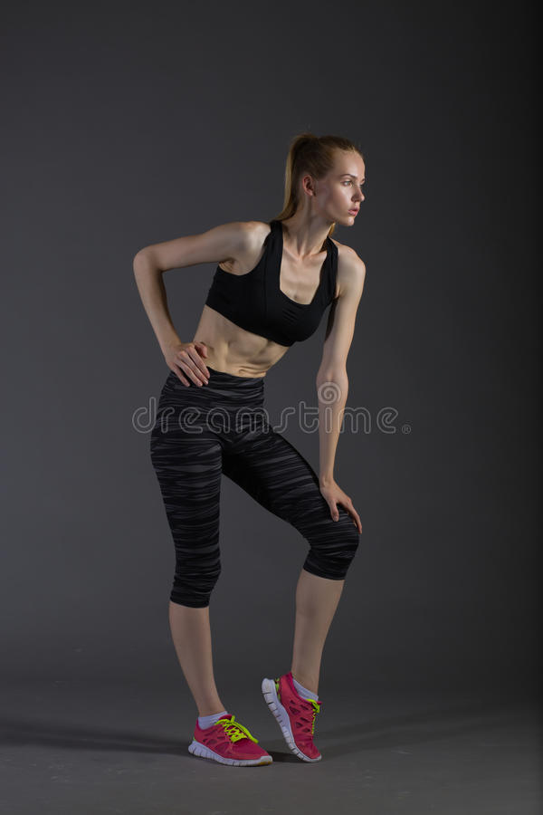 Body of slim female in activewear doing posin on gray low key, perfect blonde. Body of slim female in activewear doing posin on gray low key, perfect sport woman royalty free stock photos
