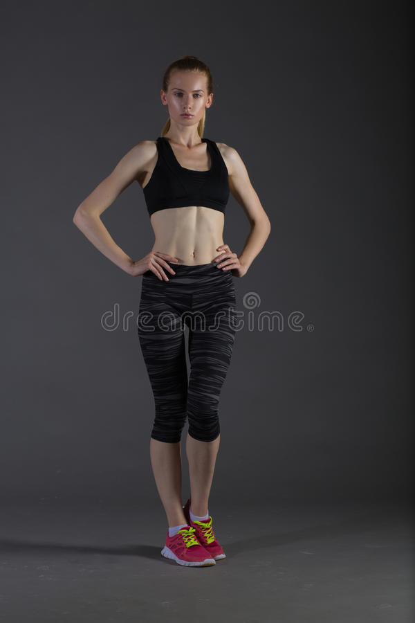 Body of slim female in activewear doing posin on gray low key, perfect blonde. Body of slim female in activewear doing posin on gray low key, perfect sport woman royalty free stock images