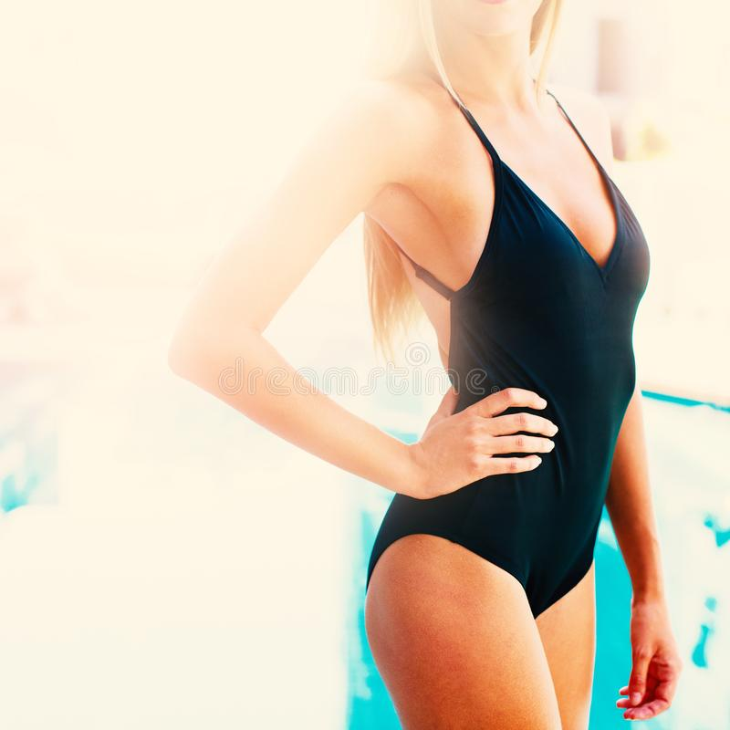 Body slim sports suntanned woman bathing suit. Body young slim sports suntanned woman black bathing suit near swimming pool summer day outdoor square toned royalty free stock image