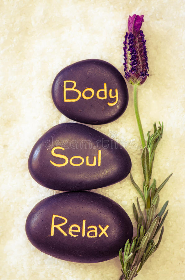 Body, soul, relax. Black lava stone with words body, soul, relax stock image