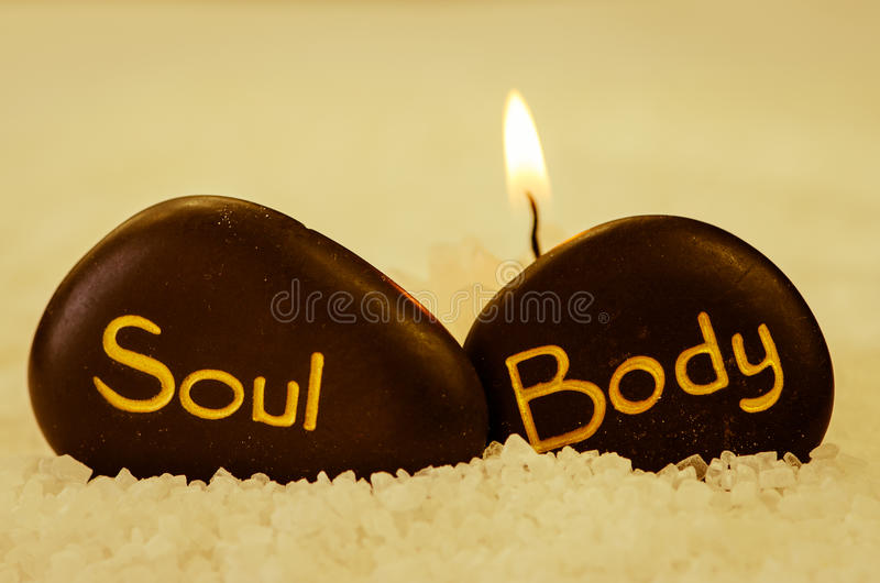 Body soul. White sea salt and black lava stone with words body and soul royalty free stock image