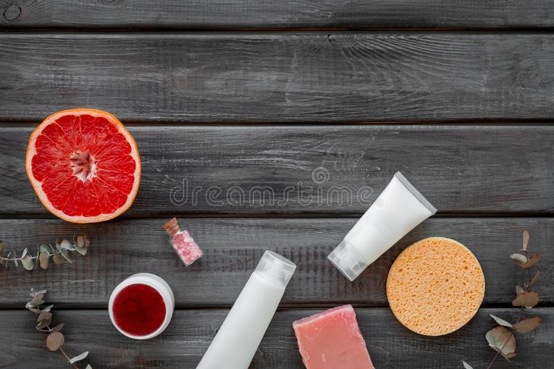 Cosmetics with natural herbal and citrus ingredients on gray wooden background top view copyspace stock photo