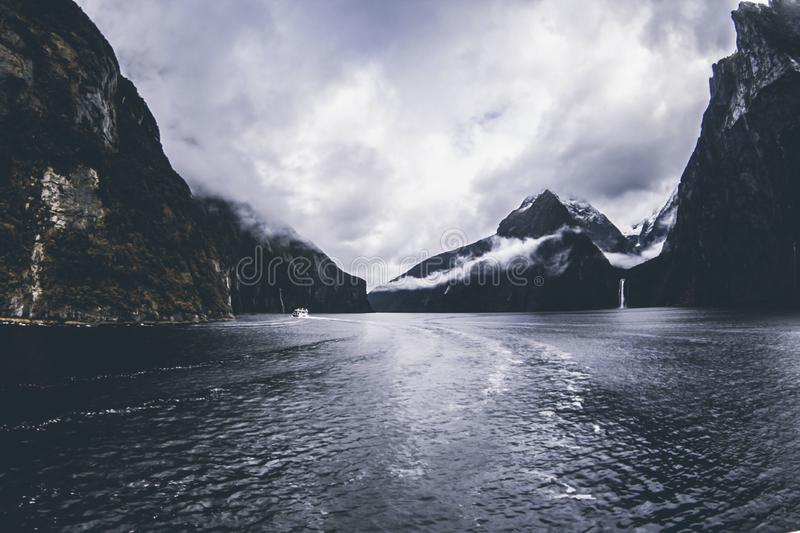 Body of Water Surround by Mountains Under Cloudy Sky royalty free stock image