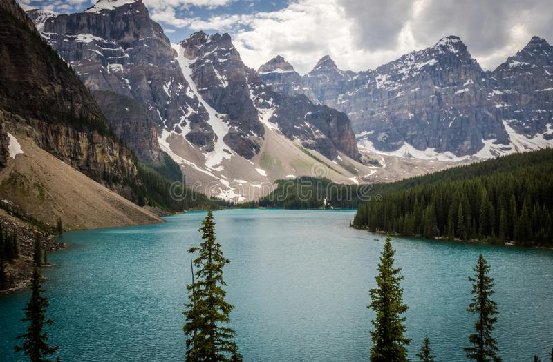 Body of Water Between Trees and Mountain at Daytime stock images