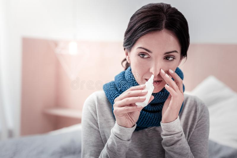 Close up of ill woman with nasal drops stock images