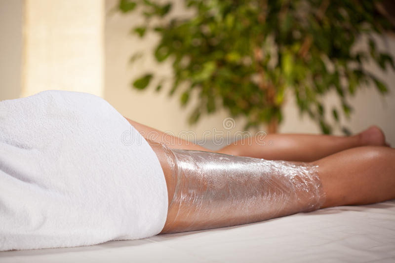 Body wrapping in spa room stock images