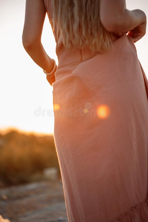 Body of young beautiful Caucasian blonde woman in pink dress in a deserted field on sunset background stock photo