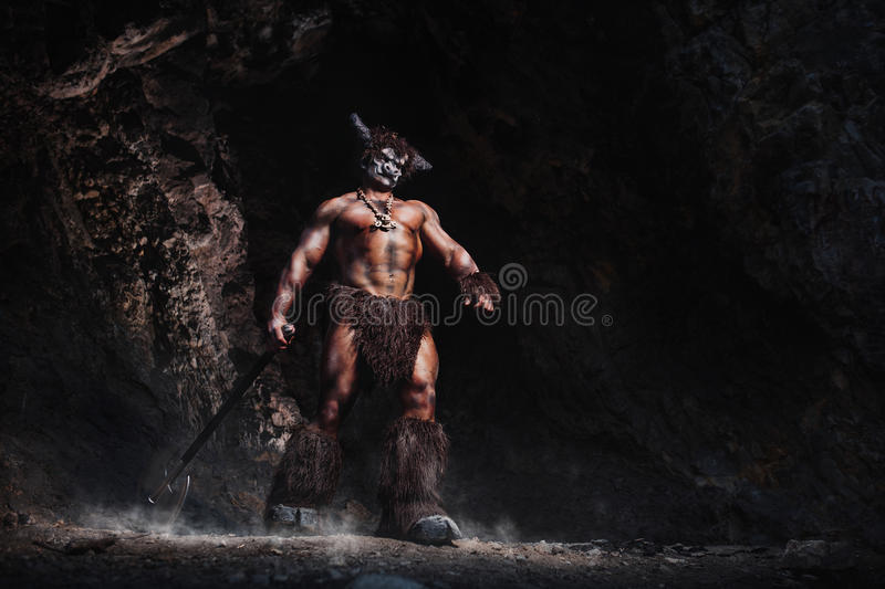 The bodyart man angry minotaur with axe in cave. The muscular bodybuilder man with angry minotaur bodyart Greek mythology with axe in cave vector illustration