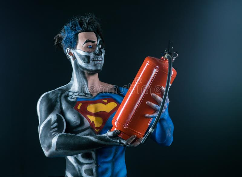 Bodyart of a super hero holding a fire extinguisher in the hands stock photography