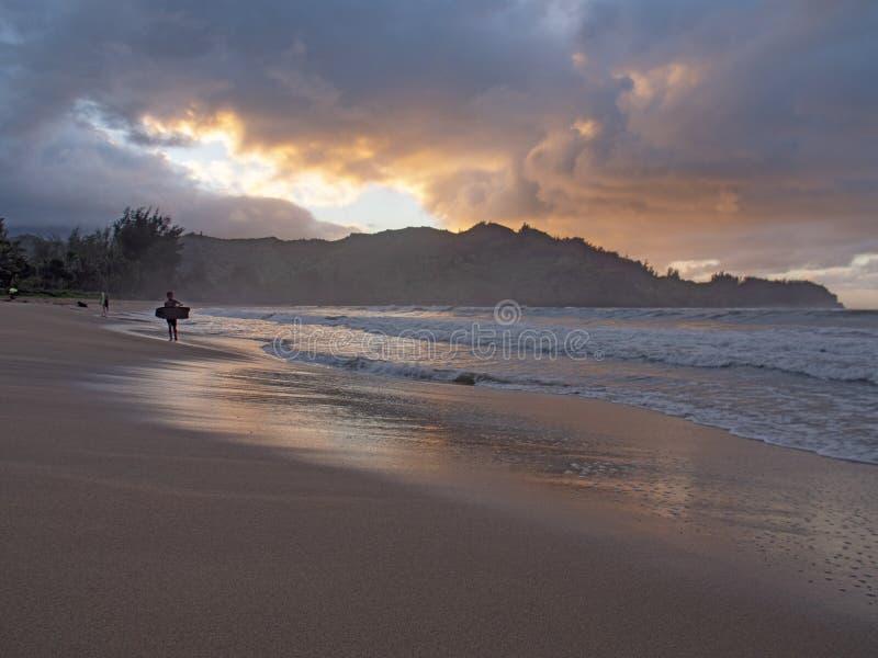 Bodyboard da terra arrendada do surfista da criança que sae do oceano no por do sol imagens de stock royalty free