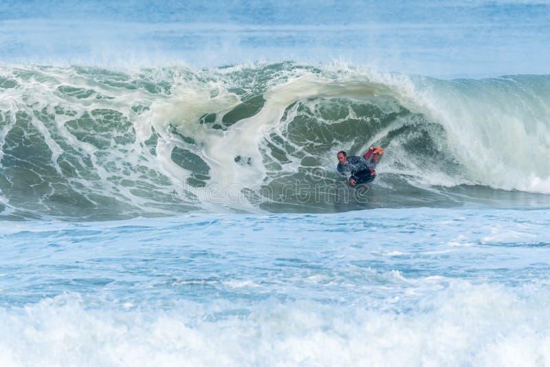 Bodyboarder die oceaangolf surfen stock afbeeldingen