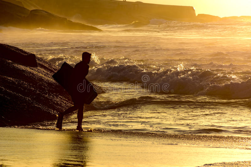 Bodyboarder going into the water royalty free stock images