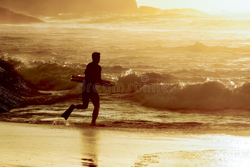 Bodyboarder que entra na água imagem de stock royalty free
