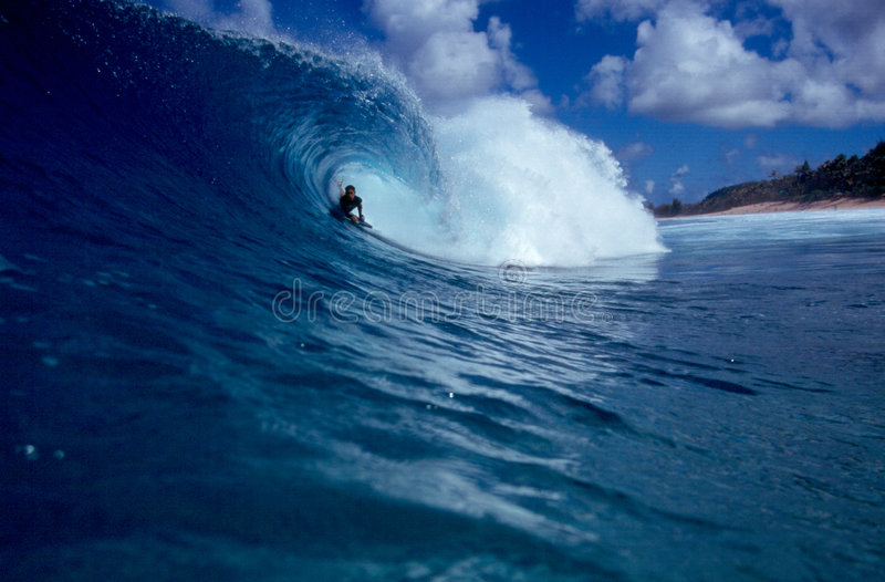 Bodyboarder Surfing a Big Blue Tube Wave. A bodyboarder rides the tube of a wave on the north shore of the island of Oahu in Hawaii stock photo