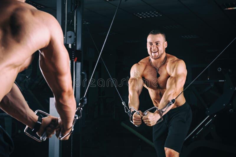 Bodybuider demonstra exercícios do cruzamento no gym fotos de stock