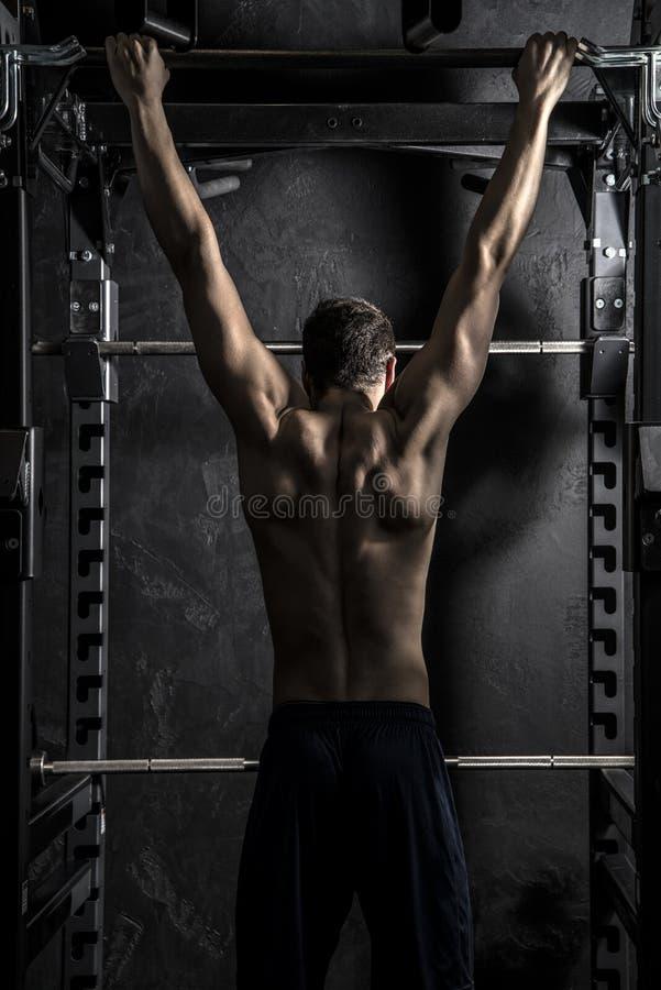 Bodybuildender starker Mann Zug-UPS auf Stange lizenzfreie stockfotos