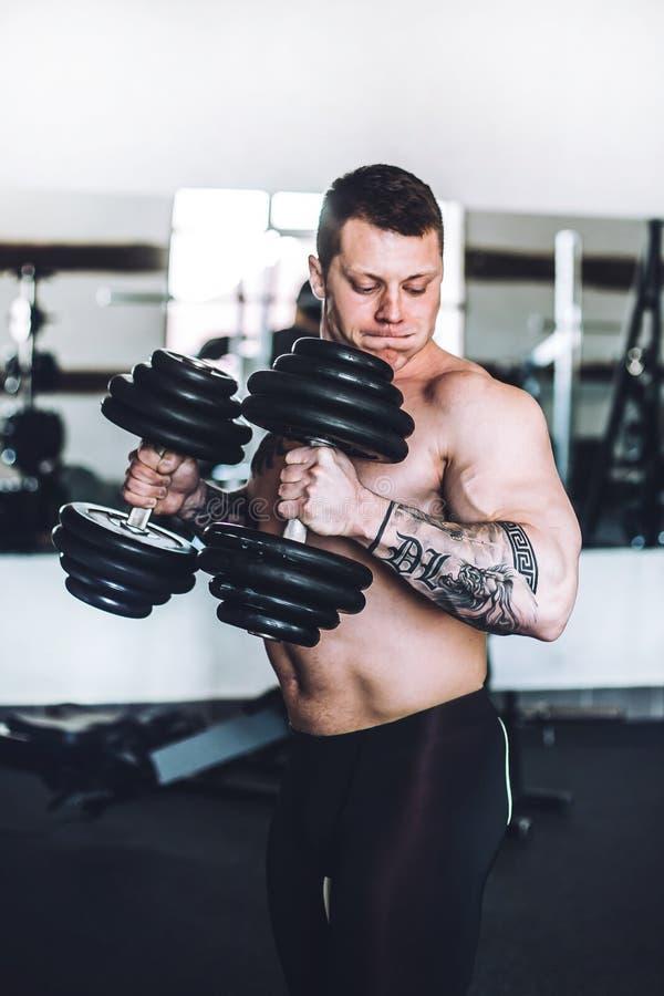 Bodybuildender Trainer auf Krafttraining im Eignungsraum stockfoto