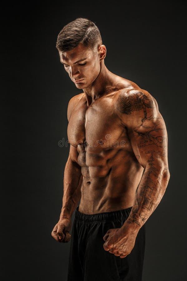 bodybuilder θέτοντας Muscled άτομο ικανότητας στο σκοτεινό υπόβαθρο στοκ εικόνα