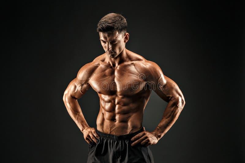 bodybuilder θέτοντας Muscled άτομο ικανότητας στο σκοτεινό υπόβαθρο στοκ εικόνες