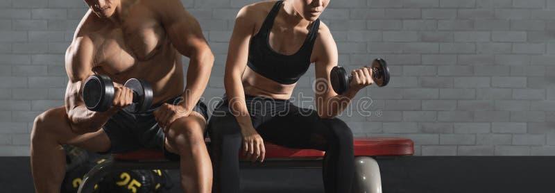 Bodybuilder που επιλύει με τα βάρη αλτήρων στη γυμναστική Το νέο ζεύγος επιλύει στη γυμναστική Ελκυστική γυναίκα και όμορφο muscu στοκ φωτογραφίες
