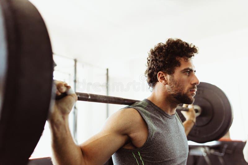 Bodybuilder που επιλύει με τα μεγάλα βάρη στοκ εικόνες
