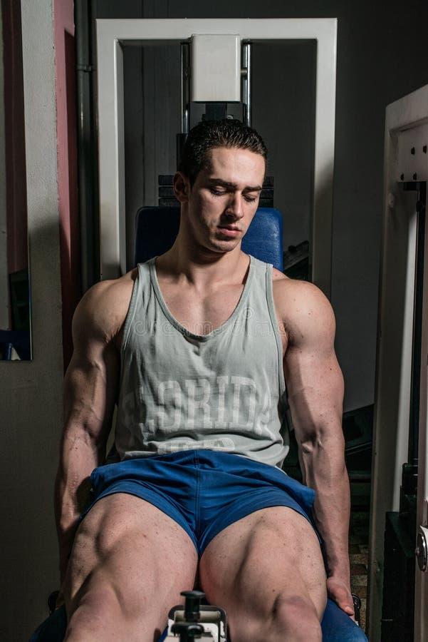 Bodybuilder που κάνει τη βαρέων βαρών άσκηση για τα πόδια στις επεκτάσεις ποδιών μηχανών στοκ φωτογραφία με δικαίωμα ελεύθερης χρήσης
