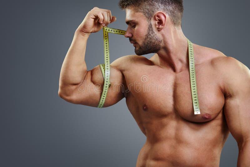 Bodybuilder που μετρά τους δικέφαλους μυς με το μέτρο ταινιών στοκ εικόνα
