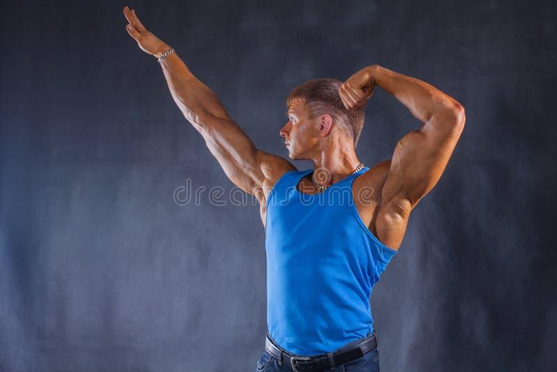 Bodybuilder στα τζιν και μια μπλε μπλούζα στοκ εικόνες