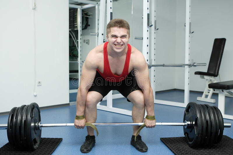Bodybuilder. The young man lifts a bar on the exercise machine in a gym royalty free stock image