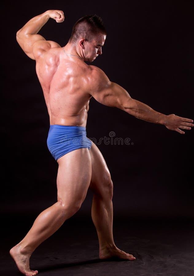 Bodybuilder. Posing is studio, flexing his lats stock photo