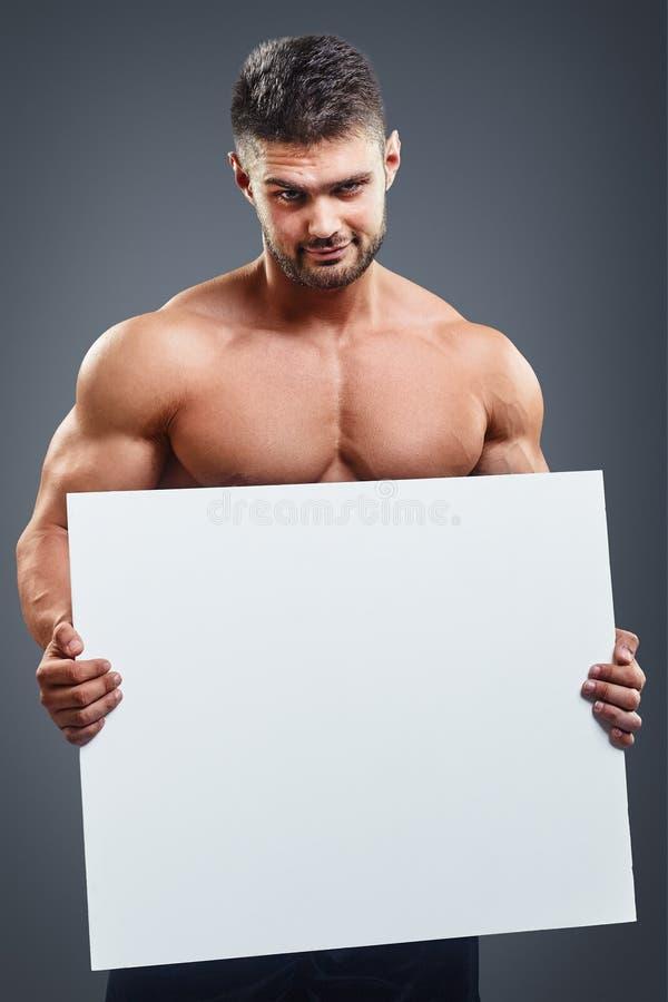 Bodybuilder avec l'affiche blanche vide photographie stock