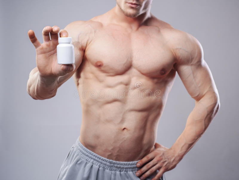 Bodybuilder avec un pot blanc de pilules sur neitral images stock