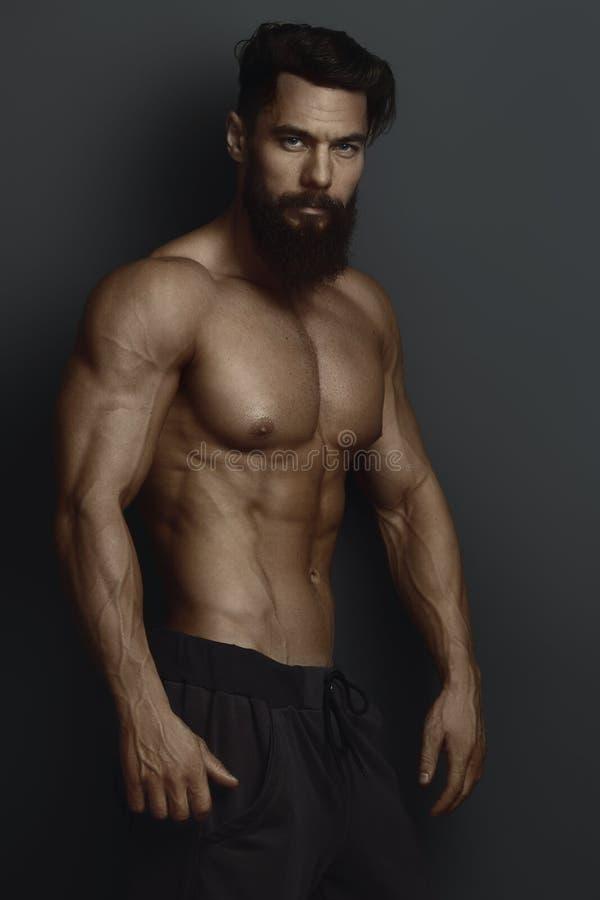 Bodybuilder barbu contre le mur foncé photos stock