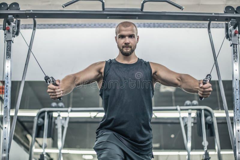 Bodybuilder caucasien beau brutal établissant dans le coffre de formation de gymnase pompant des withdumbbells de muscles pectora image libre de droits