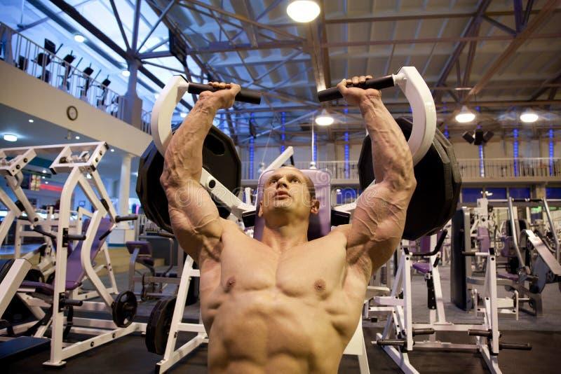 Bodybuilder che fa weightlifting in ginnastica immagine stock