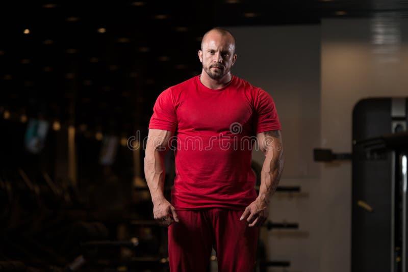 Bodybuilder che propone in ginnastica immagini stock