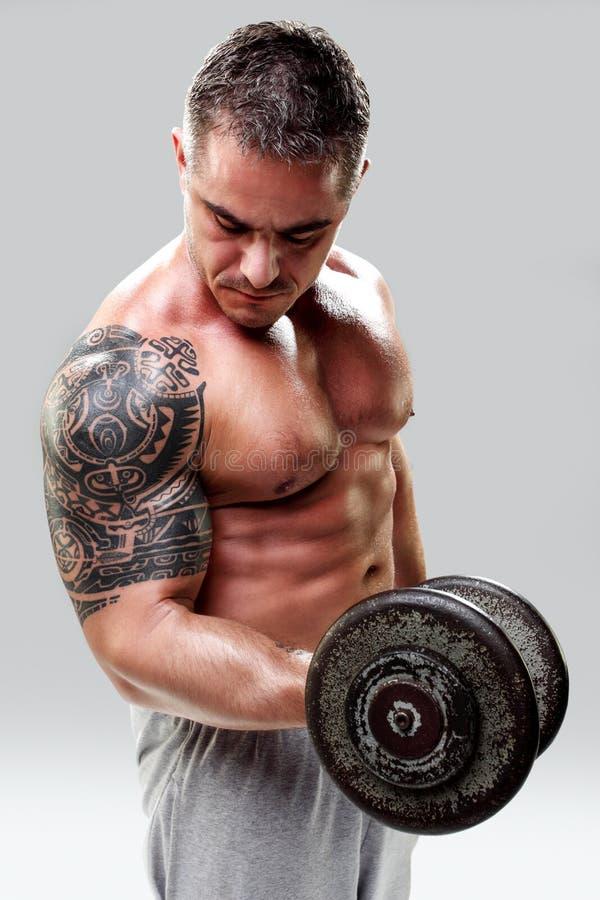 Bodybuilder con los pesos de elevación de un tatuaje, primer fotos de archivo