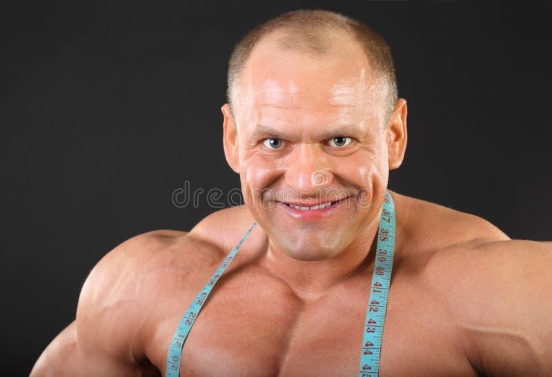 Bodybuilder con nastro adesivo di misurazione sui sorrisi del collo fotografie stock libere da diritti