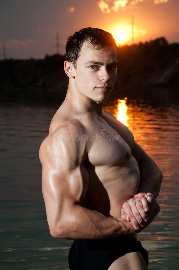 Bodybuilder con un tramonto fotografia stock